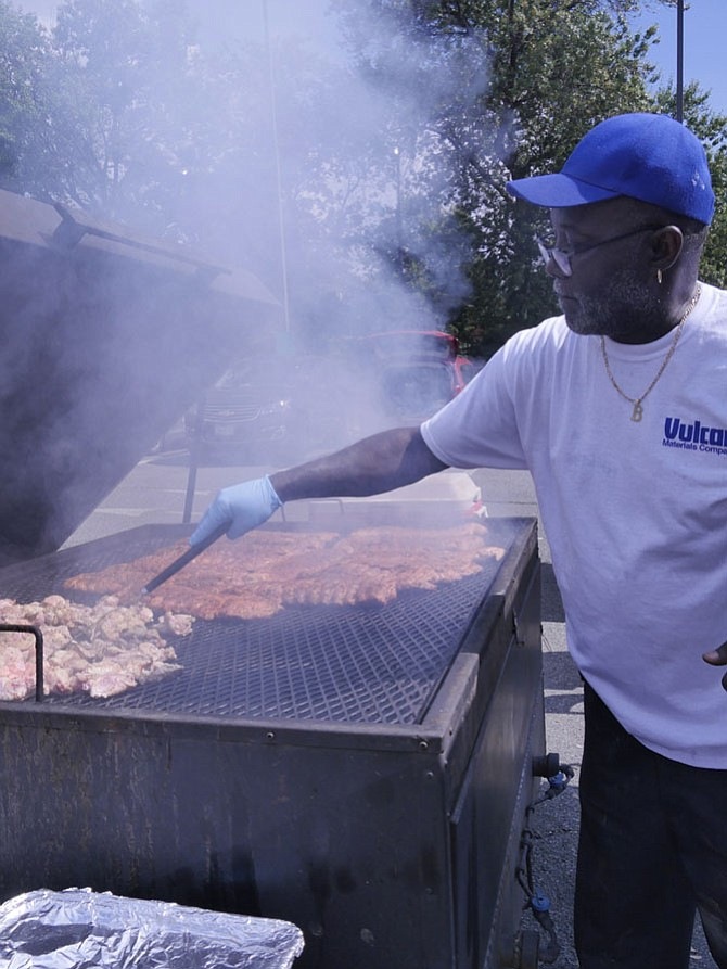 "Ed Whitehead is barbecuing ""about 20 racks of ribs"" at the 2017 Nauck Civic and Community Pride Day at Drew Model Elementary School and Community Center on Saturday, Sept. 16. Whitehead said he has to let the bone protrude, and then flip the ribs over for about another half hour. He is cooking ribs and chicken for Restaurant Depot."