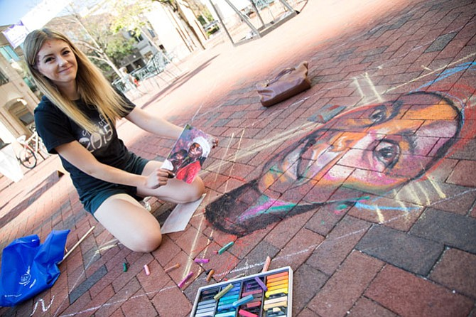 Abigail Lockhart, an art student at Shepherd University, draws a chalk mural in a professional space at ChalkFest Saturday in Reston Town Center.