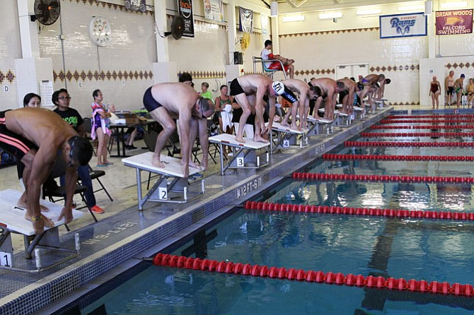 Swimmers take their starting positions on the blocks for the second heat of the 100 yard freestyle.