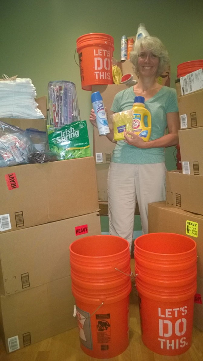 Fairfax resident Christie Johnson is knee-deep in flood buckets and up to her ears in disaster relief supplies Tuesday night as she prepares for Sunday – when her fellow churchgoers will assemble 300 personal hygiene kits and 25 cleaning buckets for the United Methodist Committee on Relief.