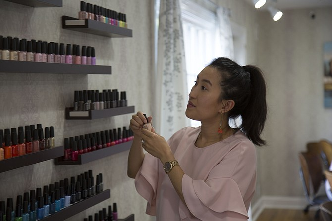 Nomin Bold, 27, helps a customer select a nail polish at her spa on Sept. 13. From Sept. 1 to 8, 10 percent of the spa's profit — $1,500 — was donated to nonprofit organizations helping with Hurricane Harvey relief efforts in Texas.