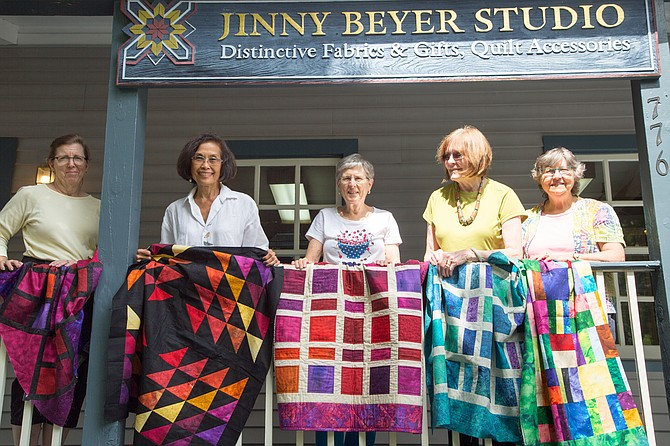 From left: Pat Blood, quilter, Carole Nicholas, Oakton resident and quilter, Marge Hughes, Great Falls resident and quilter, Jinny Beyer, owner of Jinny Beyer Studio, and Lura Alsalam, McLean resident and staff at Jinny Beyer Studio hold up quilts for donation to Hurricane Harvey Relief Tuesday at the Sew-in.