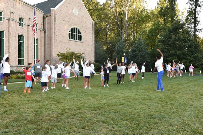 Participants in the Connelly School of the Holy Child Tiger Trot 5K run/walk warm up with Wes Dunning. Holy Child's event will benefit Cabin John Fire Department and the school's wellness programs.