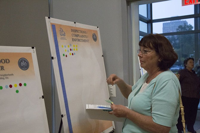 "Patricia Phillips of Fairfax, who is a proponent of short-term rentals, participates in a ""dot exercise,"" indicating topics that are her primary concerns regarding regulation. She placed her dot stickers on the boards with these four issue areas: Taxes/income/revenue; neighborhood character; inspections/complaints/enforcement; and homeowner and condominium associations."