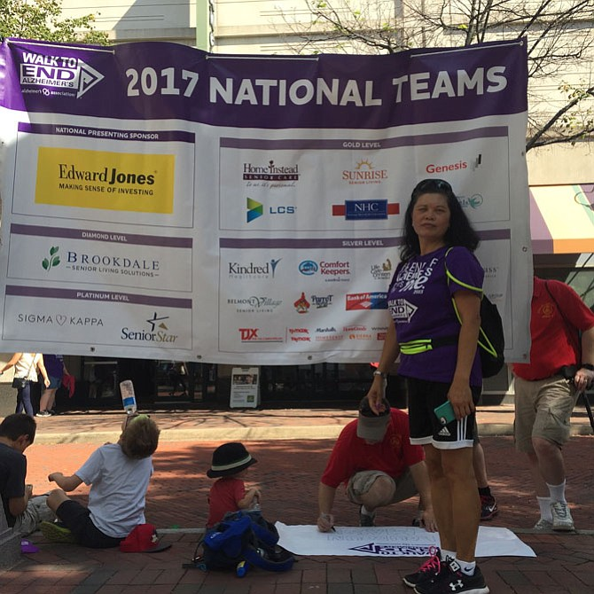 Jocelyn Herradura, a Sunrise Senior Living caregiver, stands in front of the sponsors for the Alzheimer's Walk.