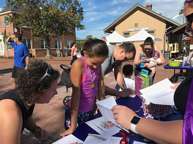 Herndon Parks & Recreation Department awarded Avalon Gallardo, 10, of Herndon a gold medal for completing all seven stations at the Family Fitness & Fun FEST held Saturday, Sept. 23 in downtown Herndon.