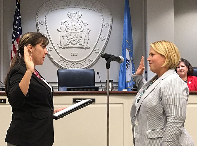 City Clerk Melanie Crowder (on left) administers the oath of office to Jennifer Passey.