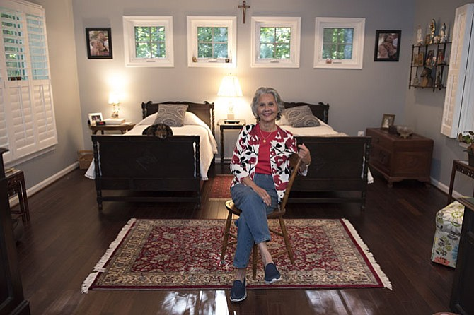 Lita Clark (who just turned 84) in the master bedroom of the in-law suite recently added to the home of her daughter Julia MacInnis and son-in-law, Jack. The room was designed to accommodate several heirlooms, including the twin beds under a course of Mi windows that assure privacy, yet allow abundant natural light.