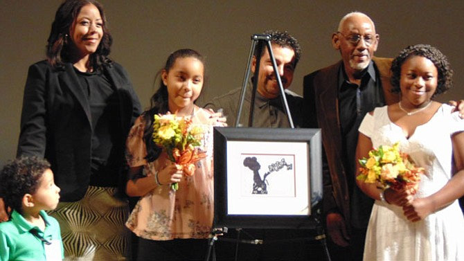 Artist Gabriela Aroche and her family with her artwork.