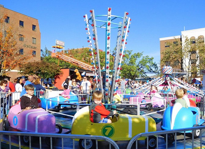 Children enjoy the carnival rides at a past festival.