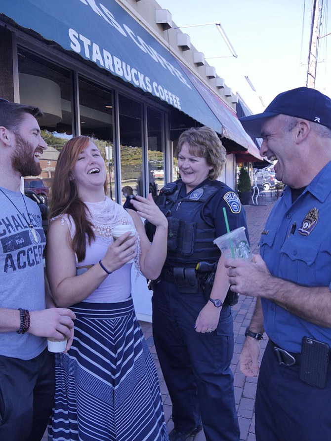 Captain David Groux chats with Alex Heimann, who has just come from Gold's Gym, and Emma Blanton. This is part of the local initiative on Oct. 4 to host an event in each police district to celebrate National Coffee with a Cop Day. Groux, who is joined by Corporal Beth Lennon, says people stop by on their way to work or after dropping off their children to have a casual conversation and a free cup of coffee on the porch compliments of Starbucks.