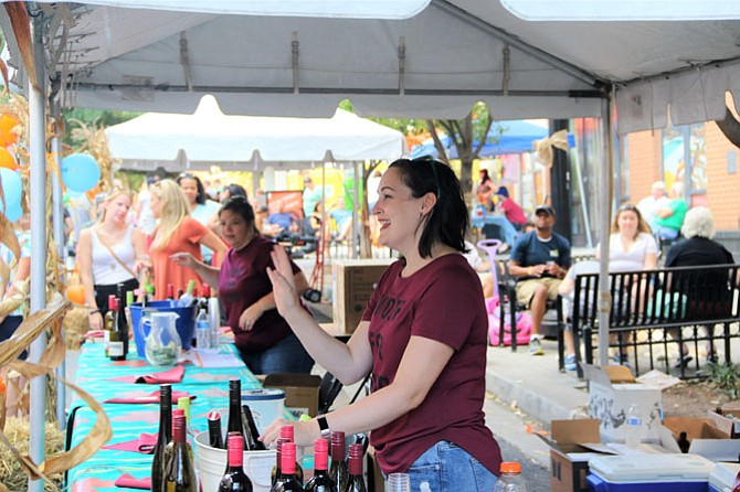 Sara Davenport of Twisted Vines Bottleshop & Bistro waves to a customer sampling the stores' wine selection at the Fall Fest.