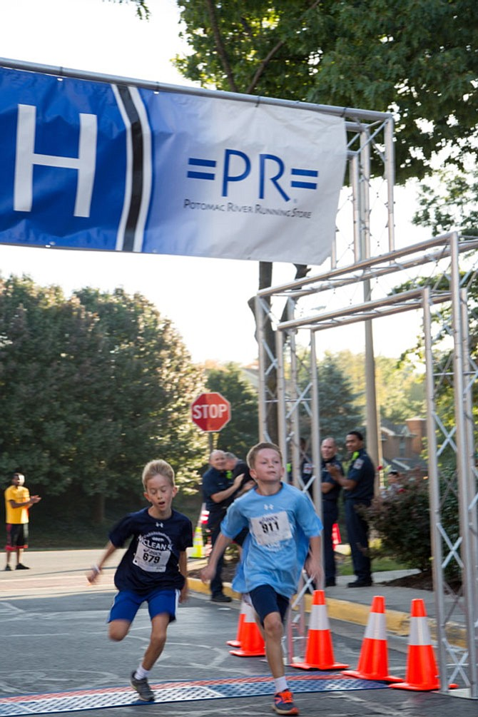From left: Liam Welch, sixth grader at Kent Gardens, and Artus Justan, a McLean resident and fifth grader at Kent Gardens, compete for the finish at the eighth annual McLean 5K race Saturday morning, Oct. 7.