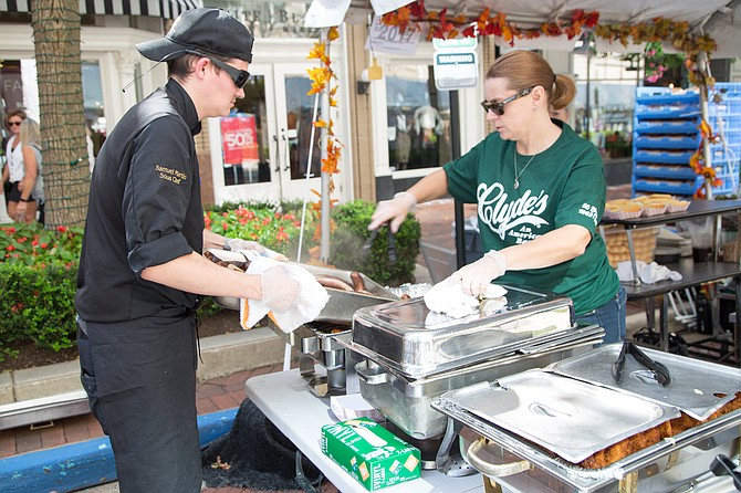 Sam Martin, sous-chef at Clyde's of Reston, helps Shannon Johnson, bookkeeper at Clyde's of Reston unload brats for the attendees at the Taste of Fall Festival in Reston Town Center Saturday, Oct. 7.