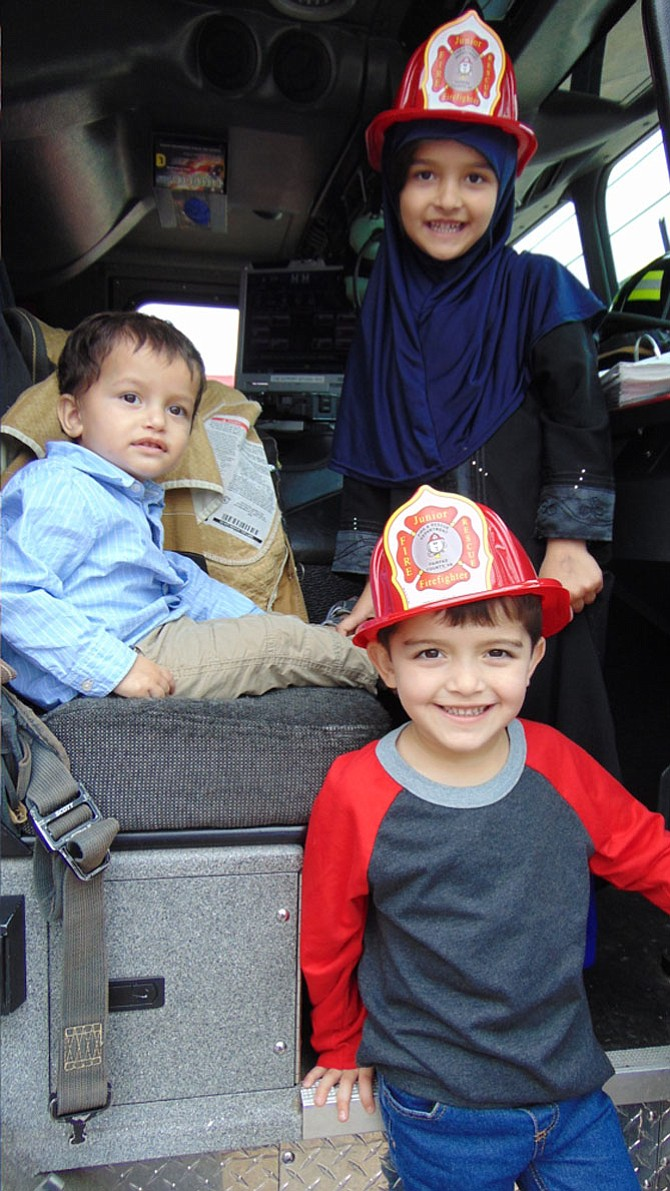 "The Shah family of Lorton — Rabia, Rehaan, and Ayan — ""ride"" inside a fire truck during the Open House at Lorton Volunteer Fire Department Company #19 on Saturday, Oct. 14, 2017."