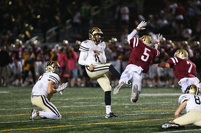 Oakton's Marcus Cruz #5 and Ryan Harris #7 attempt to block the extra point of Westfield's kicker.