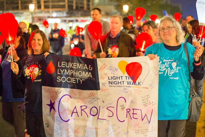 "Carol Kasson (right) and her friend Paula Kone, a Burke resident, carried a banner that said, ""Carol's Crew,"" at the Light the Night walk for Leukemia Friday night in Reston Town Center. Kasson is a cancer survivor."
