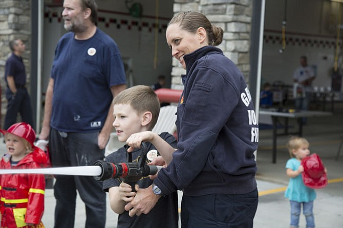 Kim Kramer of Vienna, a volunteer emergency medical technician with the Great Falls Volunteer Fire Department, gave Joe Kainec, 5, of Great Falls a turn to wield a small water hose during the open house.