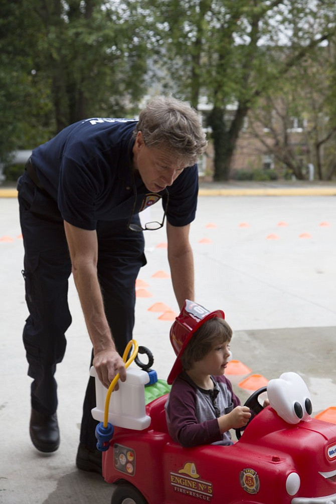 "Mac Reed of McLean, a volunteer emergency medical technician with the McLean Volunteer Fire Department, pushes Kameron Kruse, 3, of McLean through a driving course on a 22-inch tall Little Tikes ""Spray & Rescue Fire Truck,"" complete with a pressurized water tank and hose to squirt water onto a pretend fire at the end of the course."