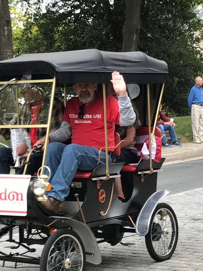 The smallest car in the Herndon Homecoming Parade 2017 belonged to Dusty Simmons and Daryl Crocker. Simmons gives a big wave to parade viewers as Crocker, a retired Town of Herndon employee, sits beside him.