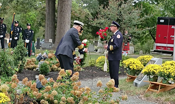 Alexandria Fire Chief Robert Dube, left, is assisted by Volunteer Fire Department president Jay Johnson (behind Dube) in laying a wreath at the Memorial to Fallen Firefighters Oct. 13 at Ivy Hill Cemetery. The ceremony is held each year during National Fire Prevention Week to honor fallen firefighters and EMS personnel.