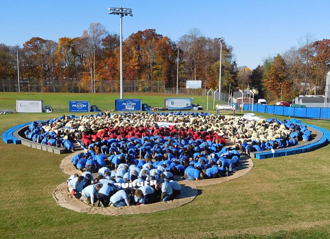 Participants crouch down according to the color of their T-shirts to create a previous year's Complete the Circle design.