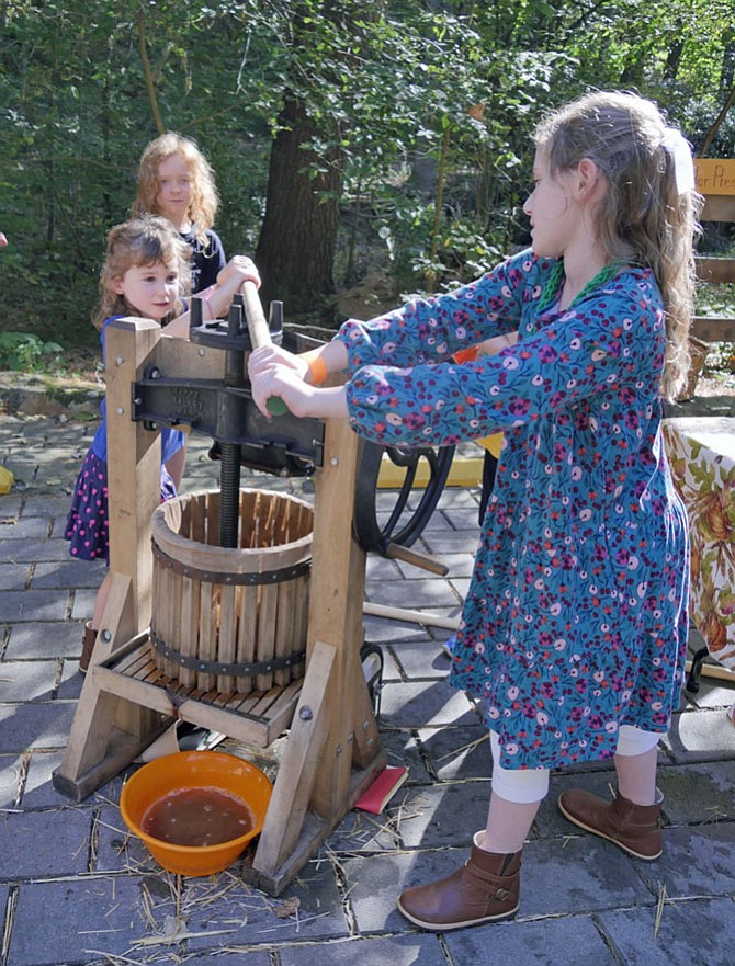 "Nine-year-old Sarah Torchinsky and her 5-year-old sister, Anna, push the wooden beam around in circles to mash a mixture of apples into cider at the Gulf Branch Fall Festival Oct. 21. Sarah says, ""This is hard to turn. You have to use all of your weight."" But it is worth the effort since cups of hot cider are available for tasting at the table nearby."