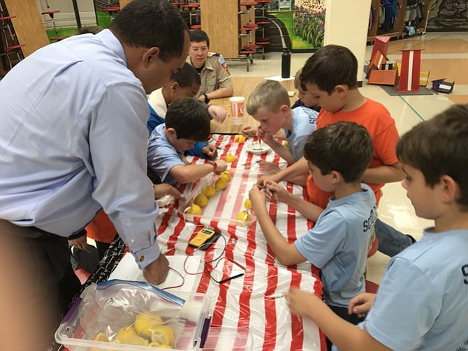 Cubs from Pack 1860 make electricity out of lemons.