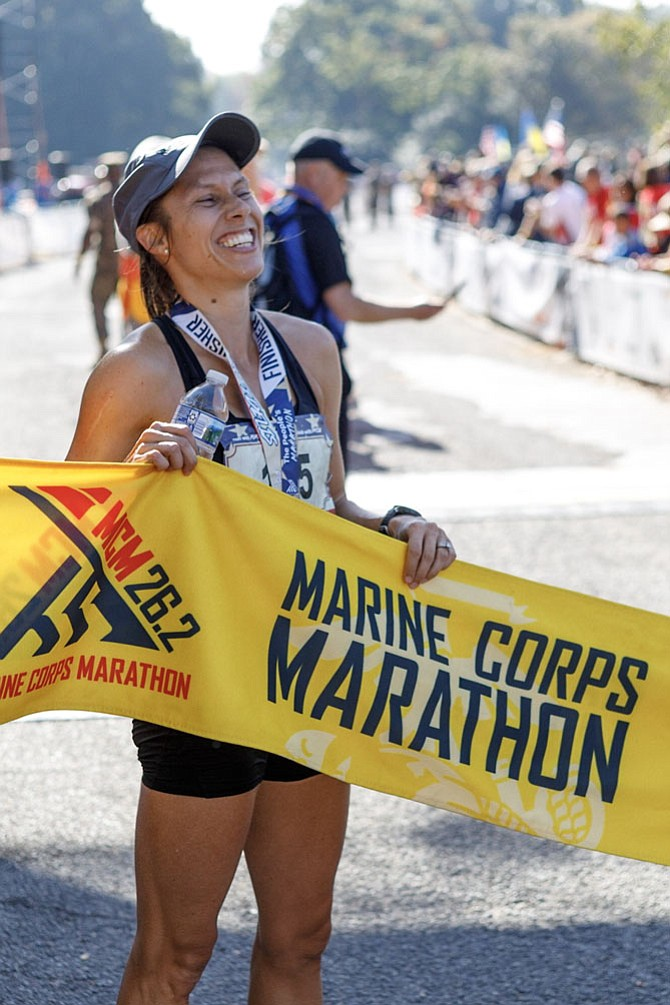 Sarah Bishop, 35, of Fairfax, celebrates holding the finish line tape after winning the women's division of the Marine Corps Marathon with a time of 2:45:06.