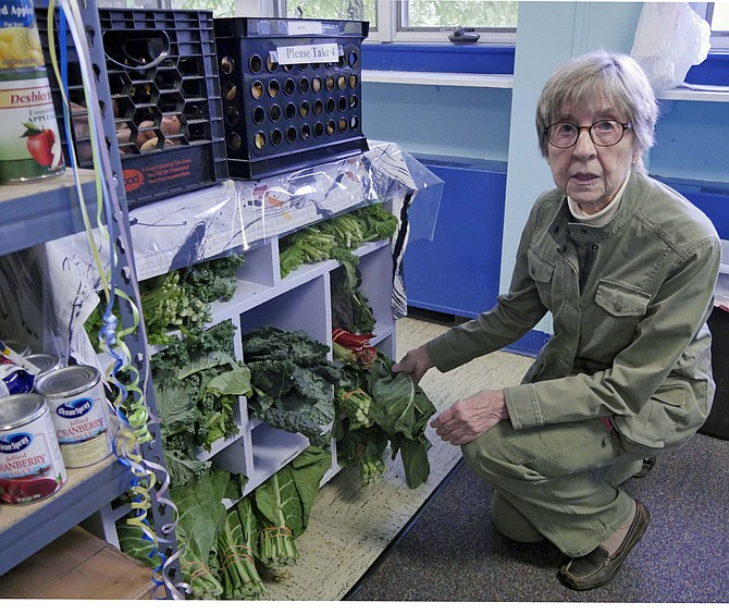 Louise Bennett, head of the West End Pantry volunteers, checks the supply of greens received from the Del Ray Farmer's Market.