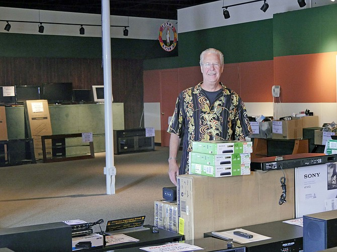 Ken Sickmen, owner of family-run Belmont TV, stands in a nearly empty showroom after announcing a closeout sale a week ago. Sickmen is closing the business after 75 years.