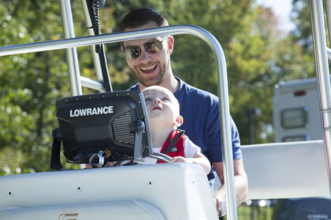Patrick Dunn of Reston sits with his son Lincoln, 1, at the helm of a boat used by the Fairfax County Police Department Special Operations Division Underwater Search and Recovery Unit during the open house.