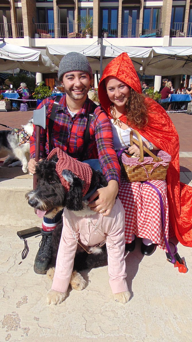 "Samantha Weisman and Kaitlin McClymont of Reston won first place as ""Best Couple"" in the Pet Costume Contest at the Boo and Brew Festival at Lake Anne with their dog Bernie dressed as Little Red Riding Hood, Grandma and the Huntsman."