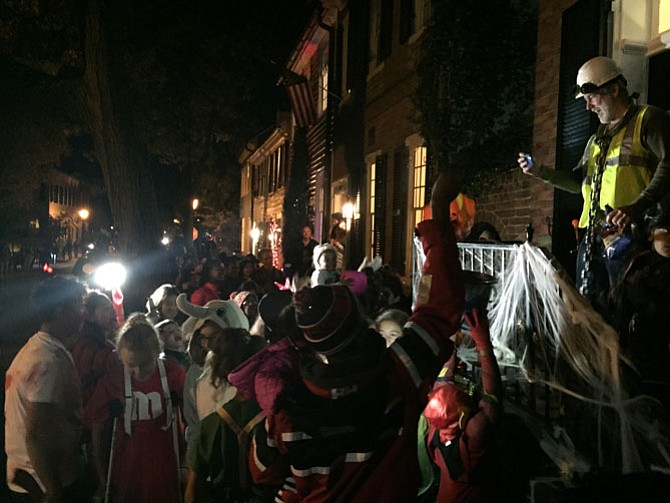 Chris Leary, a phantom construction worker, gives out candy to a crowd of trick-or-treaters.