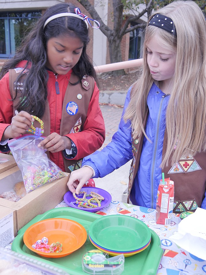 Chocolate frosted, glazed and custard-filled donuts sit on the table at the Central Library for hungry voters. Lizzie Neale (right) of Brownie Troop 6880 says the money will go for military activities and to help their troop. Meera Kuma has also made bracelets. Meera says these will sell for $2 because they take 2-3 hours to make.
