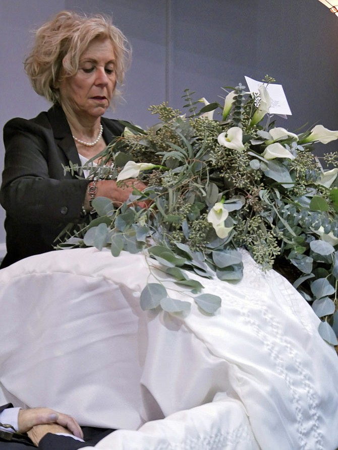 Janet Barnett places flowers on a casket.