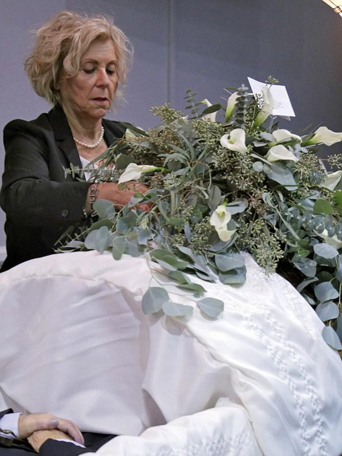 Janet Barnett places flowers on a casket.