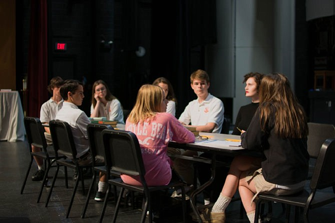 "Bishop Ireton students in rehearsal for ""Twelve Angry Jurors"" (from left): Kevin McNerney (Juror # 8), Jake Carlo (Juror # 10), Kathleen McNerney (Juror # 7), Anna Johnson (Juror # 12), Roxanne Fisher (Juror # 5), Andrew Holland (Juror # 4), Olivia Hays (Juror # 3), and Emily Graham (Foreman)."