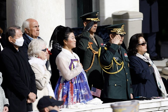 Michelle WinSook, center, of the Korean War Women's Veterans Association, places her hand over her heart during the singing of the U.S. National Anthem at the Veterans Day ceremony at Arlington National Cemetery.  This year's ceremony gave special recognition to Korean War veterans.