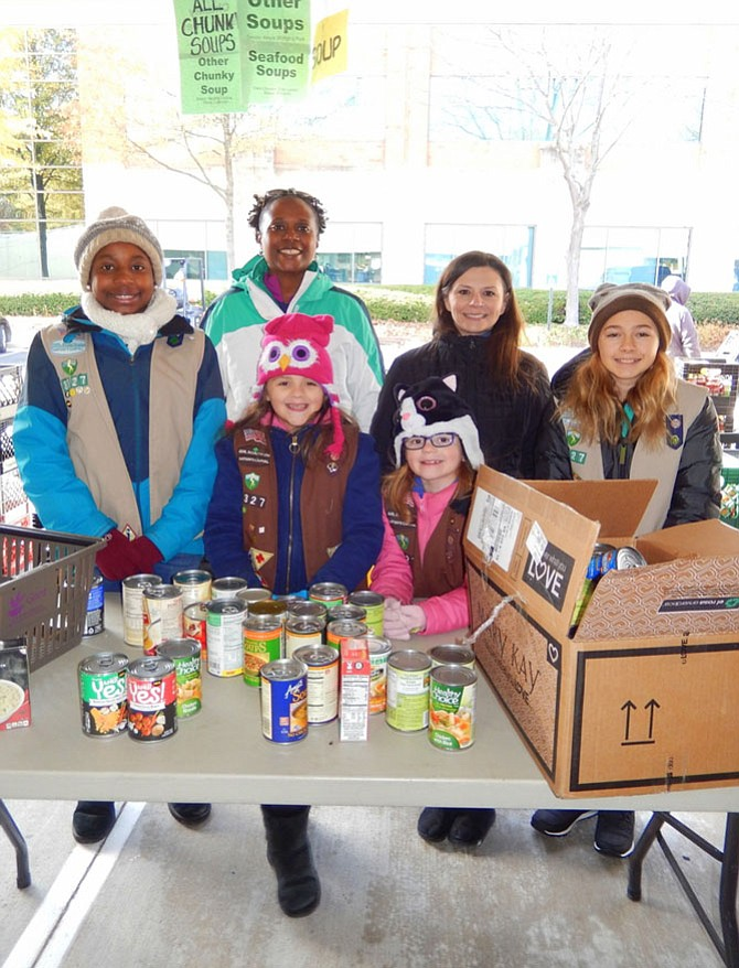 Sorting canned goods with Girl Scout Troop 3327 of Chantilly are (back row, from left) Brianna Mosely, 13; mom Tanesha Mosely; Jeanine Blomberg and Ruth Moran, 11 and (front row, from left) sisters Morgan Blomberg, 9, and Phoebe Blomberg, 8.