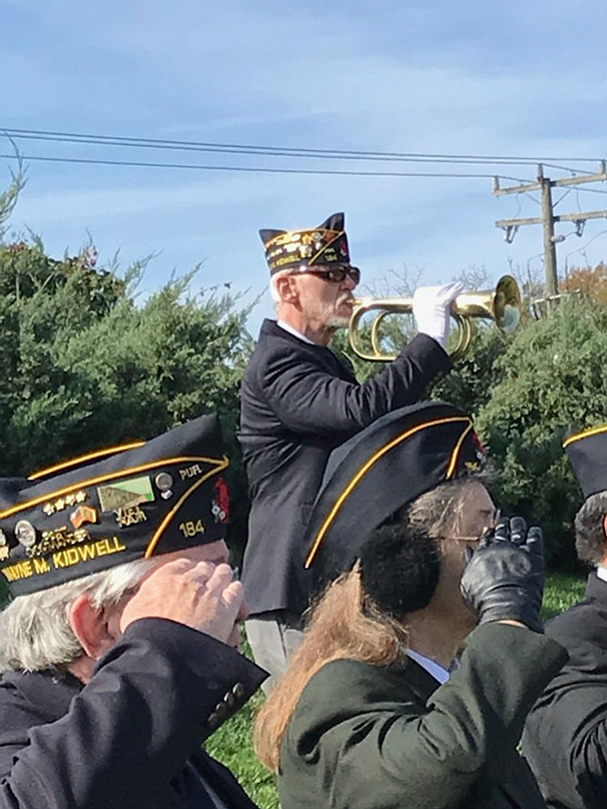 Robert Thompson, bugler and First Vice Commander of American Legion Post 184 sounds Taps at the Herndon Veterans Day Observance. As Veterans saluted and civilians bowed their heads, the 24 notes of the National Call of Remembrance echoed over the Town Green.