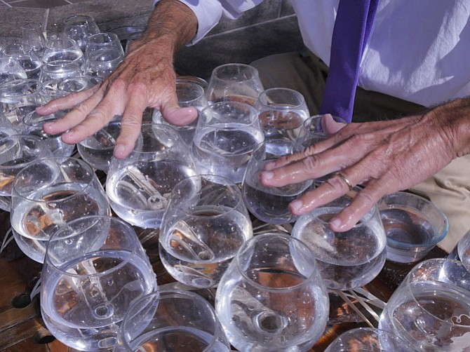 Jamey Turner uses different fingers to get the chords and the overtones on the glass harp that he plays at the corner of King and Union.