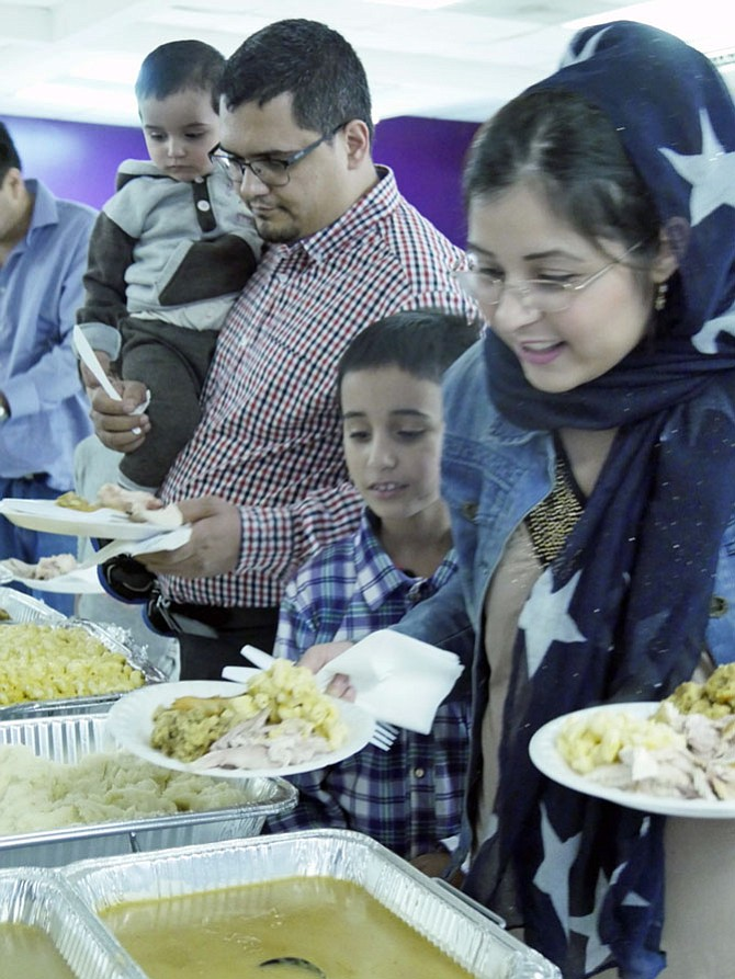 A refugee family chooses from among more than 30 dishes at the ECDC annual First Thanksgiving Dinner at the ECDC Community Center on N. Highland on Nov. 19. They examine the traditional corn pudding and head for the spicy red lentils. The dishes range from grilled chicken from Sudan, El Salvadoran pupusas, Afghan rice and lentils and American turkey and mac and cheese.