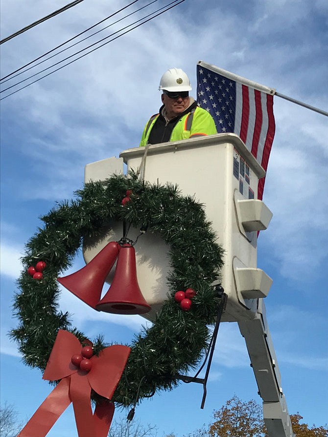 Johnny Johnson, Herndon Department of Public Works, exchanges one of the American flags flown in Observance of Veterans Day for one of Herndon's vintage-style Holiday Wreaths.