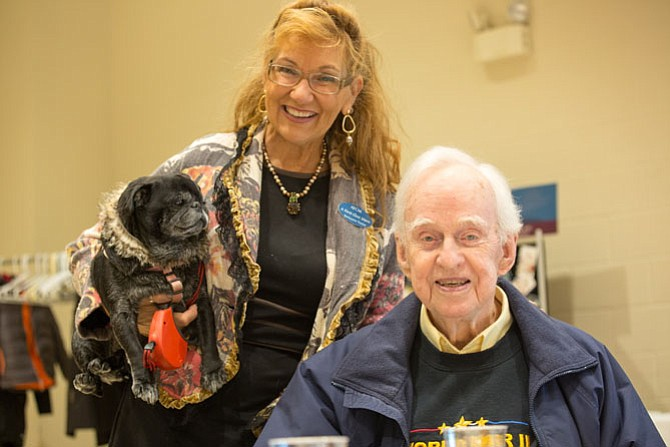 "Beckyanne Theriot, the owner of ""A First Class Move,"" a local moving company that sponsored the event and Richard Kirkland, an Air Force WWII and Korean War veteran. Theriot brought her pug Pearl to the Thanksgiving meal at Our Lady of Good Counsel Church on Tuesday, Nov. 14 in Vienna."