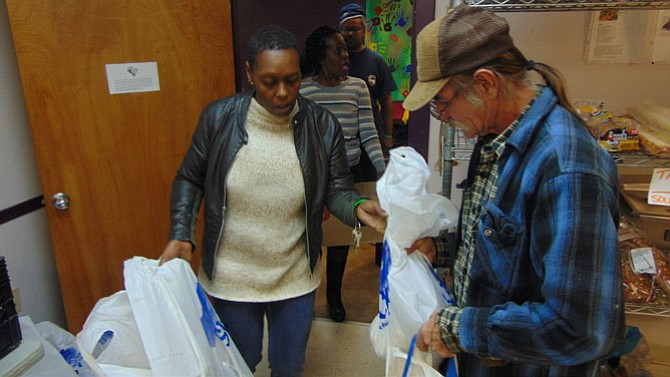 Rising Hope Food Pantry Manager Melissa Lee assists Ray Schonasky of Mount Vernon with his bags of food.
