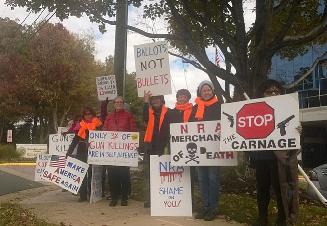 Activists against gun violence line the sidewalk Nov. 14 in front of the headquarters of the National Rifle Association at 11250 Waples Mill Road in Fairfax, where they hold protest signs for passing motorists as part of their awareness campaign. This regular gathering is an open-action protest and signs are provided to those who want to participate on the 14th of each month.