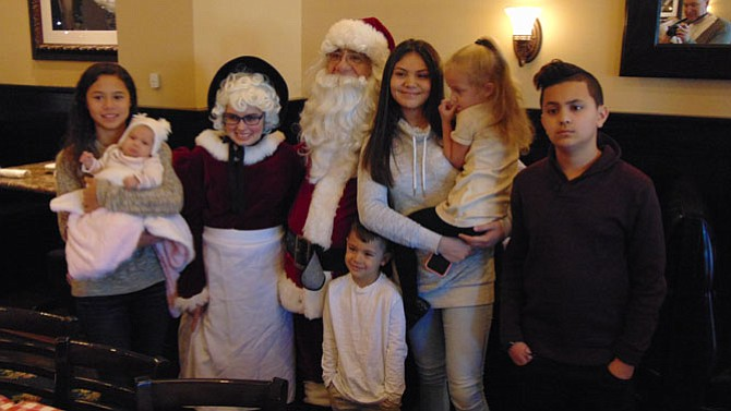 Faith, Melina, and Moe Hamdan, Jaida and Alex Garcia, and Sadie Garrett of Springfield with Santa and Mrs. Claus.