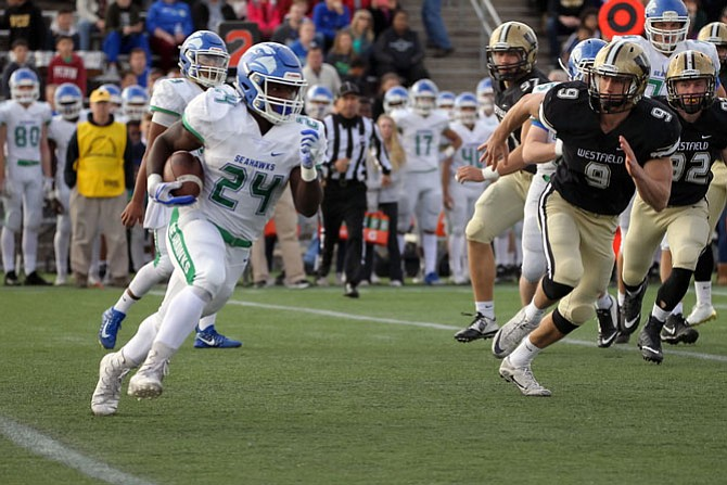 Albert Mensah #24 carries the ball for South Lakes while Westfield's Aaron Dishun #9 pursues.