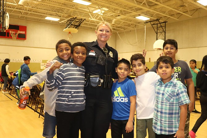 Crime Prevention Specialist SPO Denise Randles poses with students at Herndon Elementary School's Thanksgiving Feast.